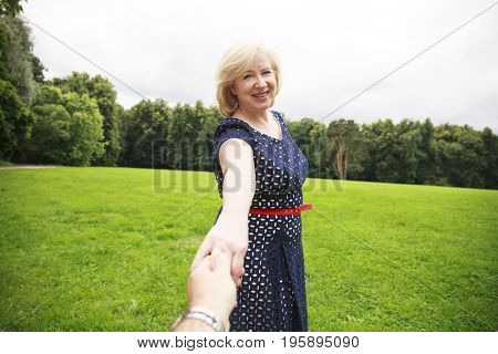 Follow me. Portrait of lovely middle aged blonde woman in the summer park