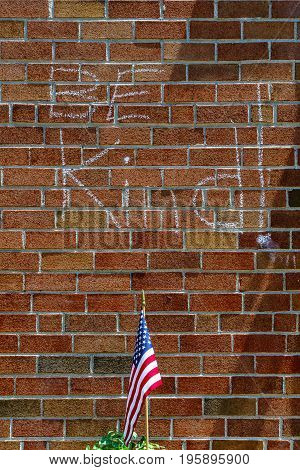 Red brick wall chalk inscription Be Kind and flag of the USA texture New Hope PA