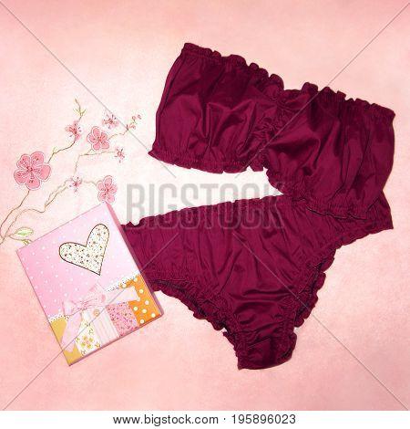 Woman underwear burgundy set bra panties on pink floral towel