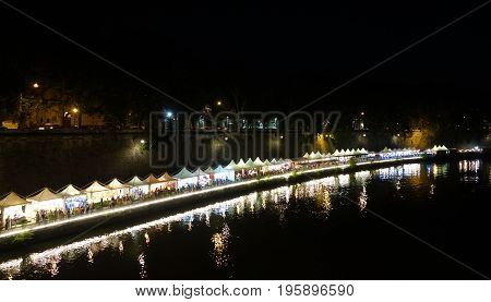 ROME ITALY - JUNE 25 2017: Lungotevere near the Tiber Island people enjoy the summer night among trendy bars