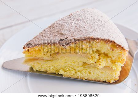 Homemade apple cake biscuit close up of a slice of cake on white plate on white wooden background