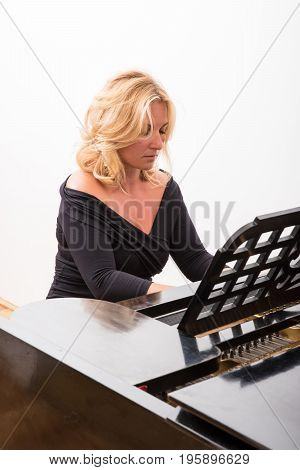 Elegant classical musician woman playing on piano.