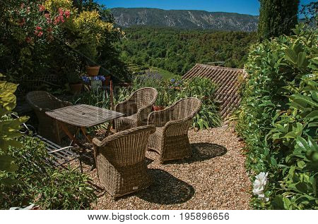 View of small garden with mountains and sunny blue sky in the background, at the village of Ménerbes. Located in the Vaucluse department, Provence-Alpes-Côte d'Azur region, southeastern France