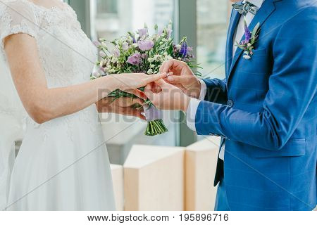 The bride and groom exchange rings. The bride puts the ring on the groom. The groom puts the ring on the bride.