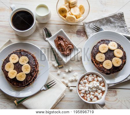 Breakfast for couple included oat pancakes with banana, nutella, honey, with coffe and milk and cacao with marshmallow on white wooden background