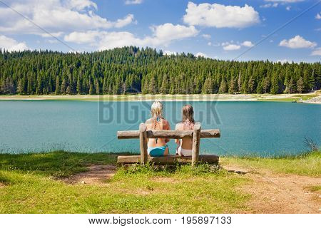 rear view of two girls on a bench made of logs near the lake