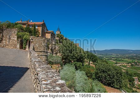 Panoramic view of street, house and hills of Provence under sunny blue sky, at the village of Ménerbes. Located in the Vaucluse department, Provence-Alpes-Côte d'Azur region, southeastern France