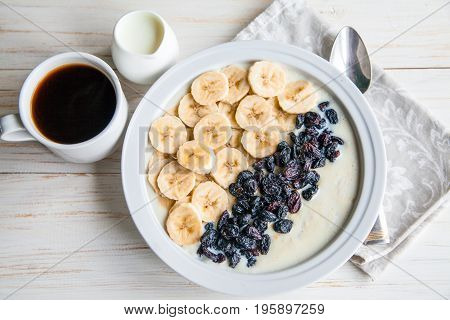 Fitness diet healthy Breakfast which included oatmeal oat porridge with milk, banana and raisins without sugar and fat with cup of coffee with milk on the white wooden background
