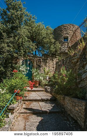 View of staircase and gate with flowers and sunny blue sky in the background, at the village of Ménerbes. Located in the Vaucluse department, Provence-Alpes-Côte d'Azur region, southeastern France