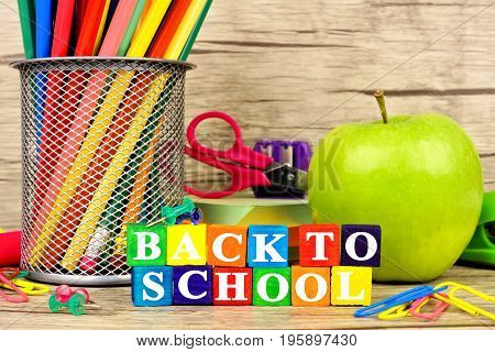 Close Up Of Colorful Back To School Wooden Blocks With School Supplies Against A Rustic Wood Backgro