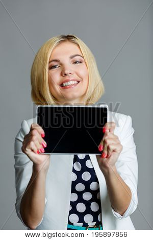 Smiling young model holds tablet