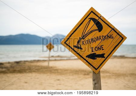 Kiteboarding sign wooden kitesurfing signpost on a beach at adriatic sea in Croatia. Inspiring kitesurfer silhouette sport and recreation concept.