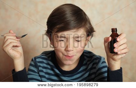 preteen boy take sore medicine with spoon and bottle