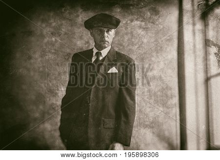 Retro 1920S English Gangster Wearing Flat Cap And Suit. Standing Next To Window.