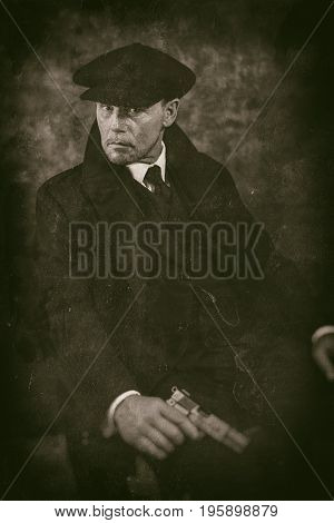 Retro 1920S English Gangster With Gun Sitting On Chair. Peaky Blinders Style.