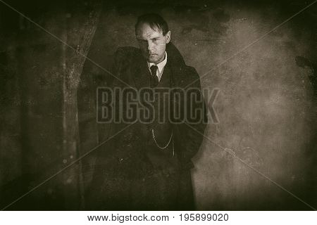 Retro 1920S English Gangster Standing Against Wooden Pole. Peaky Blinders Style.