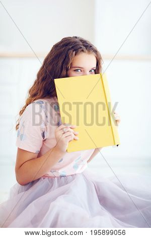 Beautiful Young Girl Hiding Face Behind The Book