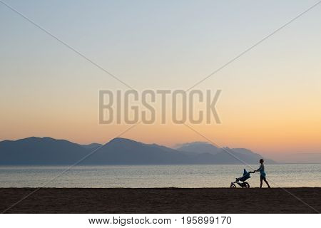 Silhouette of mother with stroller enjoying motherhood at sunset landscape. Walking or jogging woman with pram on a beach at sunset. Beautiful inspirational mountains landscape.