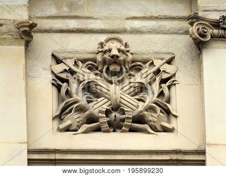 worn decorative old stone carving of a lions head fasces and palm leaves on halifax town hall with surrounding columns carved in sandstone