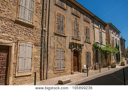 View of typical stone houses and shops on a street of the historical village of Lourmarin. Located in the Vaucluse department, Provence-Alpes-Côte d'Azur region, southeastern France