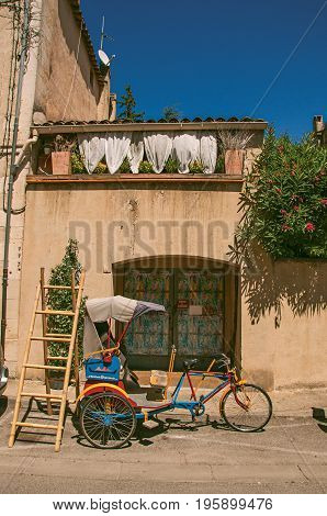 Close-up of house and colorful rickshaw on a street of the historical village of Lourmarin. Located in the Vaucluse department, Provence-Alpes-Côte d'Azur region, southeastern France