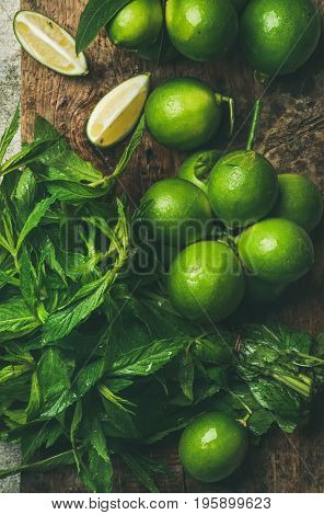 Flatlay of freshly picked organic limes and mint leaves for making cocktail or lemonade on wooden rustic board background, top view, close-up