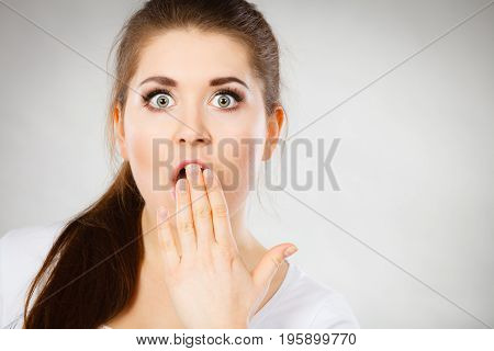 Shock face expressions concept. Closeup of shocked amazed woman covering mouth with hands