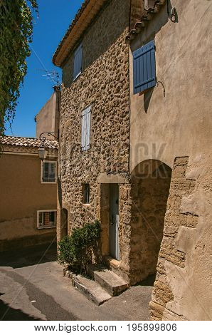 View of typical stone houses with sunny blue sky, in a raised alley of the historical village of Lourmarin. In the Vaucluse department, Provence-Alpes-Côte d'Azur region, southeastern France