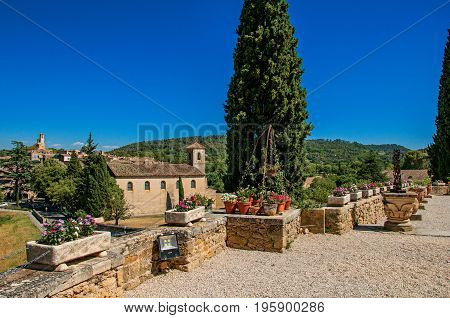 Panoramic view of Lourmarin village and hills in the background, viewed from a flowery garden. In the Vaucluse department, Provence-Alpes-Côte d'Azur region, southeastern France