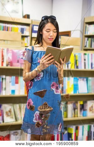 Asian Girl Reading In A Bookstore