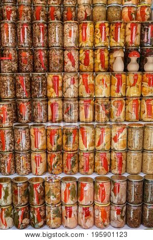 Handicraft canned jars with mushrooms paprika and other vegetables are stand on the shelf