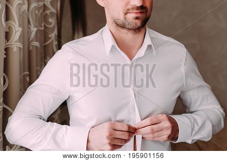 Close up of a anonymous man gets ready for work by buttoning up his business shirt. Groom's morning preparation before wedding. Horizontal