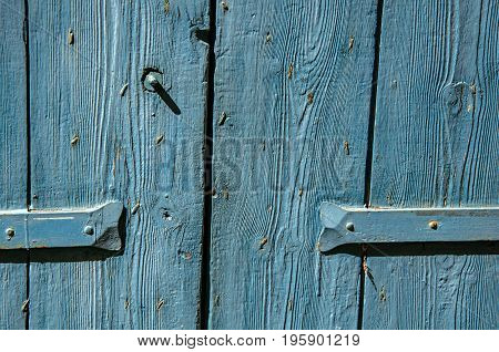 Close-up of wooden door and hinge painted blue, in the village of Lourmarin. In the Vaucluse department, Provence-Alpes-Côte d'Azur region, southeastern France