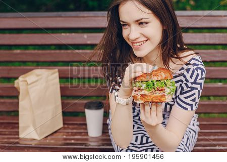 young model enjoying the break and eating a Burger