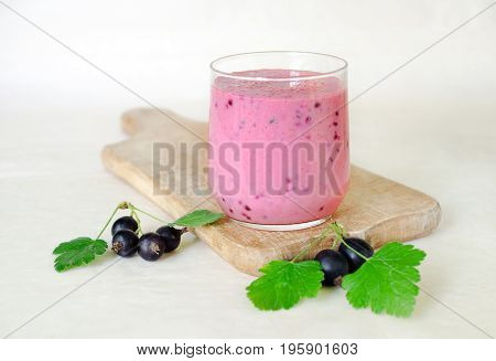 Milkshake with black currant berries in a glass cup on a wooden board with bunches of black currant. light background. side view