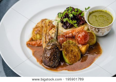 Fresh steamed vegetables served on the white plate with mashed potatoes nad sauce