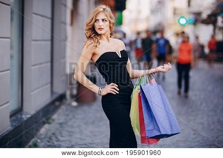 young model walks through the city and is engaged in shopping in the elegant dress