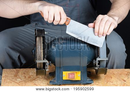 Man In Working Clothes Professionally Sharpens A Meat Cleaver Kitchen