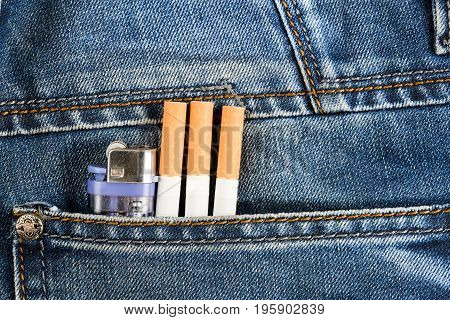 Three cigarettes and a lighter in the back pocket of your jeans. the concept of bad habits Smoking