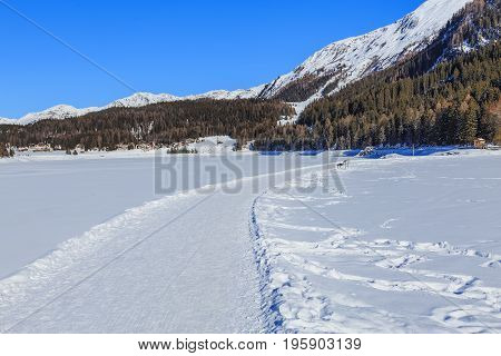 Wintertime view from the town of Davos in the Swiss canton of Graubunden: walkway along frozen Lake Davos, summits of the Alps covered by snow in the background.