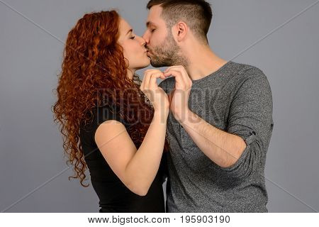 A nice young couple holding each other and shaping a heart with their hands