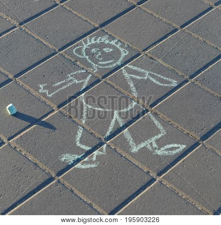 Funny drawing of a man by chalk on the asphalt