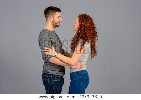 A beautiful young couple standing face to face and holding each others hands