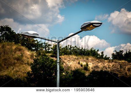 Street lamp working on cloudy daylight Europe