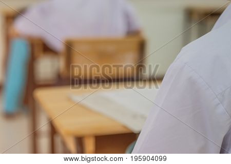 Asian boy students sittingl on wood desk with Exams paper sheet or test paper in class room education concept
