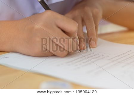 Blurred of Asian girl students hand holding pen writing fill in Exams paper sheet or test paper on wood desk in class room education concept