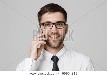 Business Concept - Portrait young handsome cheerful business man in suit talking on phone looking at camera. White background. Copy Space.