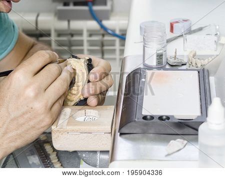 Closeup Of Dental Technician Applying Ceramic To Teeth, Implant Before Putting Into The Furnace