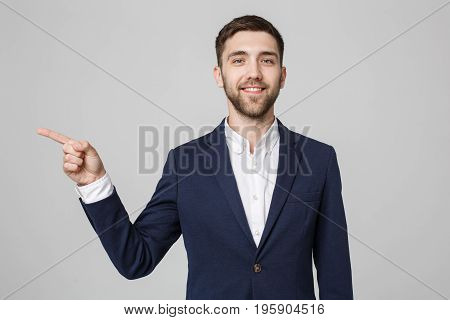 Young successful businessman pointing direction with finger over dark grey background. Copy space.