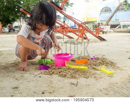 Little Asia girl sitting in the sandbox and playing whit toy shovel bucket and she was scooping in toy shovel bucket. Playing is a learning development and build muscle for children.